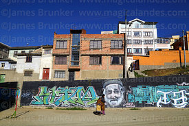 Women walking past portrait of old man on wall of residential suburb, La Paz, Bolivia