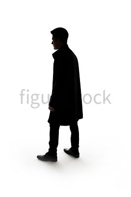 A Figurestock image of a mystery man standing, holding a gun, in silhouette – shot from eye level.