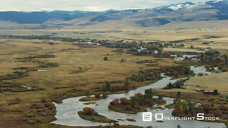 The Madison river winds through the bright autumn colors of changing Cottonwood, scrub oak and grasses in the Madison Valley, southwestern Montana