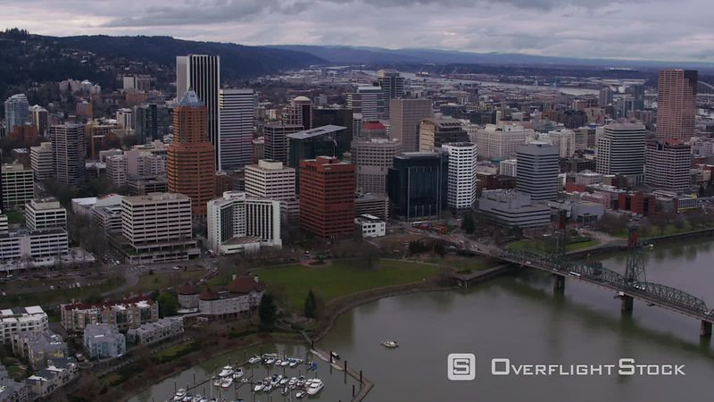 Fly from Willamette River to downtown city buildings in Portland, Oregon