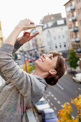 Smiling on balcony leaning back woman taking selfie