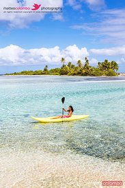 Tourist kayaking in the blue lagoon, Tikehau, French Polynesia