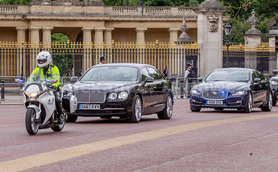 Cars carrying members of the royal family drive past Buckingham Palace