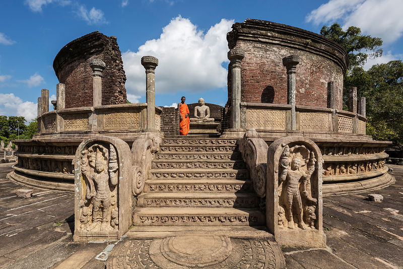 A Buddhist Monk Stands at the top of the Steps to the Vatadage temple