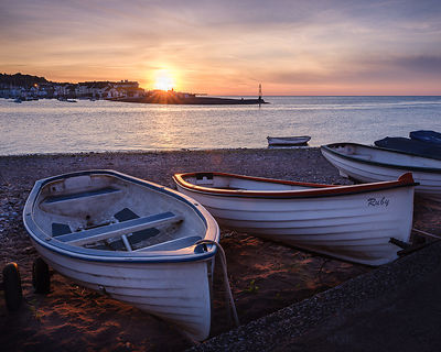 Boats at sunrise looking across entrance to Teign estuary to Teignmouth at Shaldon, Devon, UK