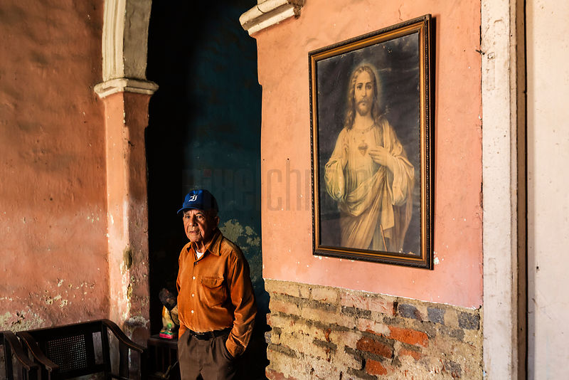 Man in his Home with a Painting of Jesus on his Wall