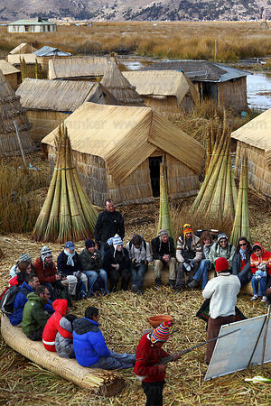 Tourists visit the Uros floating reed islands , Lake Titicaca , Peru