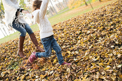 Girl running with mother in autumnal leaves