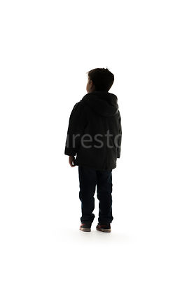 A silhouette of a boy standing in a coat- shot from mid level.