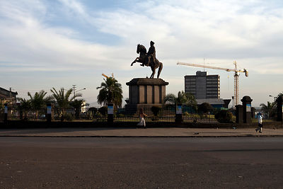 Ethiopia - Addis Ababa - People pass by the statue of Menelik II and a crane undertaking reconstruction of the city