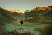 Hiker watching sunrise over lake and mountain landscape