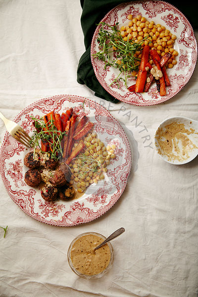 Swedish meatballs garnished with bechamel sauce and micro-greens with chickpeas and caramelized carrots