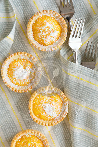 Lemon tartlets with forks on a blue and yellow striped napkin.
