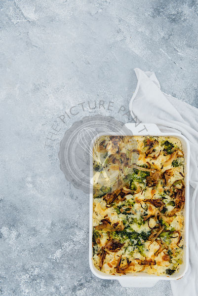 A vegetarian cauliflower and broccoli casserole served in a white casserole pan photographed on a grey background from top view.