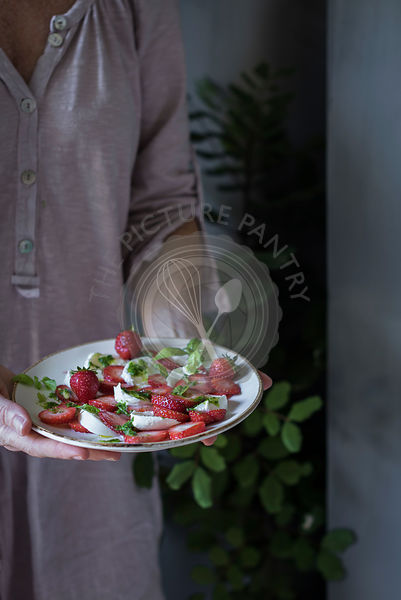 Woman holding strawberry salad with mozzarella cheese