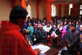 Priest leading mass inside church during Alasitas festival, Puno, Peru