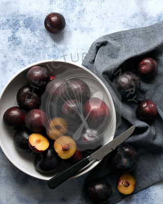 A bowl of red plums with two cut in halves and a knife.