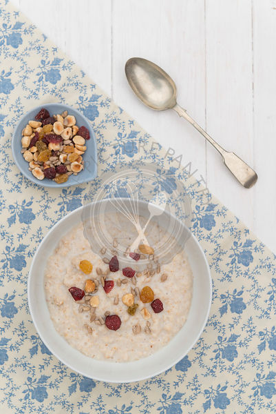 A breakfast of porridge oats srved in a white bowl on a white wooden background.