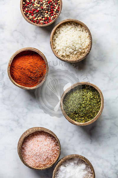 Set of spices on rustic murble background. Coconut shell bowls with paprika salt parsley and pepper. Cooking concept