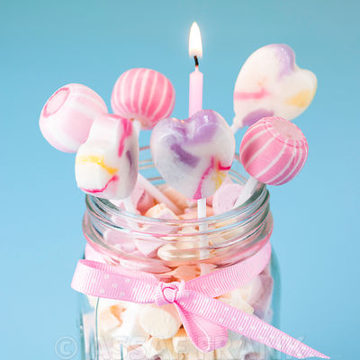 Sweets jar with lollipops and a birthday candle
