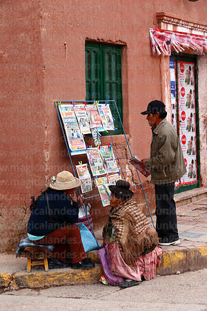 Women chatting next to newspaper stall on street corner outside colonial house, Lampa, Peru