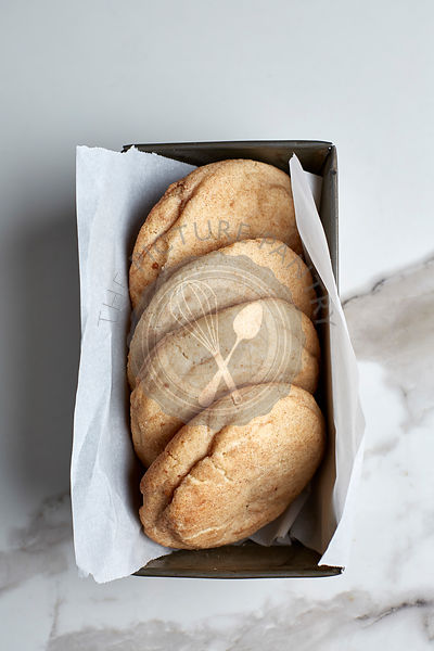 Snickerdoodle cookies in a vintage tin with parchment paper on white marble table