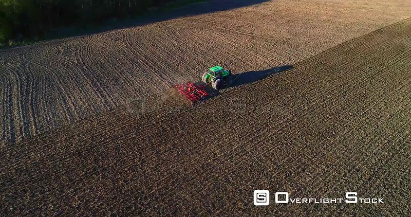 Tractor Plowing, Aerial View Around a Plow Machine Sowing, Sunny Spring Sunset, Evening Dawn, Uusimaa, South Finland