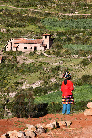 Young Quechua girl and adobe building under construction near Chinchero, Cusco region, Peru