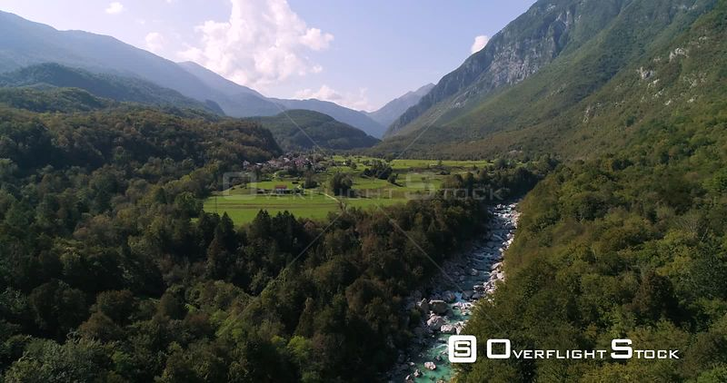Alpine rapids, C4K aerial drone view over turquoise soca river, towards a small town, in the alp nature, near Trigolov national park, on a sunny summer day, in the Julian alps, Slovenia
