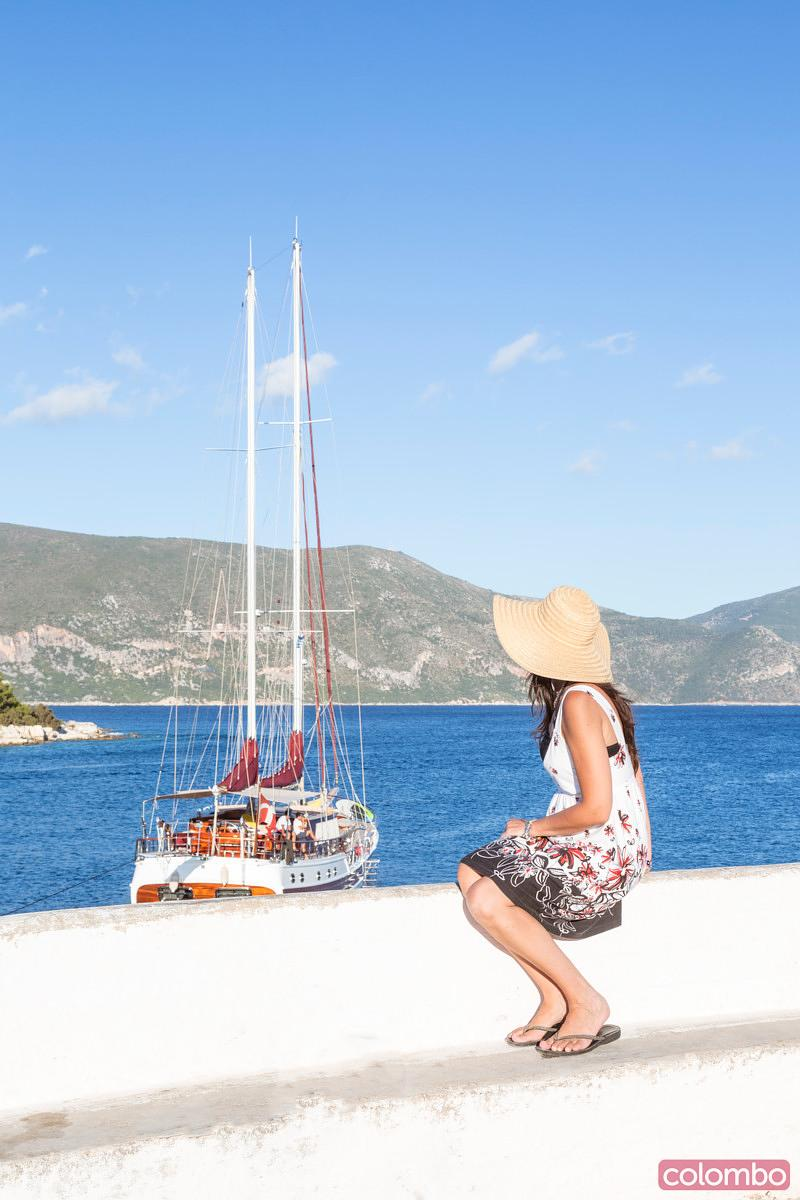 Woman looking at sail boat in the harbour of Fiskardo. Kefalonia, Greek Islands, Greece