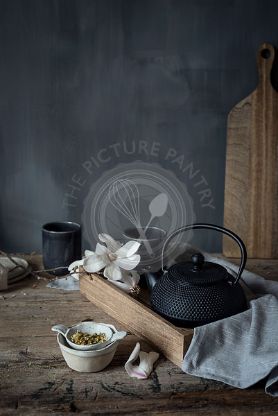 Tea in a black teapot on a rustic kitchen table