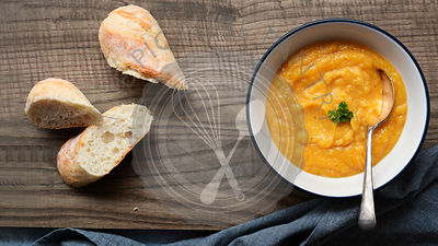 A bowl of homemade pumpkin soup of a wooden cutting board with pieces of crusty bread.