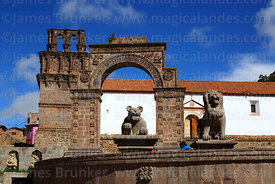 Puma and lion statues in plaza in front of entrance archway and Nuestra Señora de la Asunción church, Juli, Puno Region, Peru