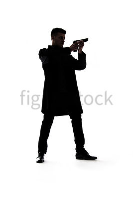 A Figurestock image of a mystery man standing, painting a gun, in silhouette – shot from low level.
