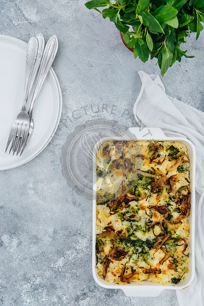 A vegetarian cauliflower and broccoli casserole served in a white casserole pan photographed on a grey background from top view. Fresh herbs, white plates and forks accompany.