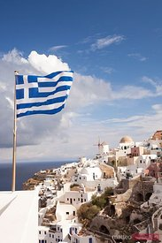 Greek national flag waving, in the village of Oia, Santorini, Greece