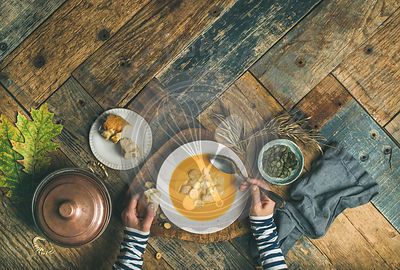 Flat-lay of female hands and Fall warming pumpkin cream soup with croutons and seeds over rustic wooden table background