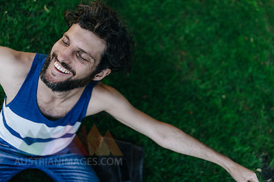 Happy man sitting on a meadow in park