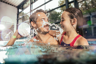 Happy father with daughter splashing in indoor swimming pool