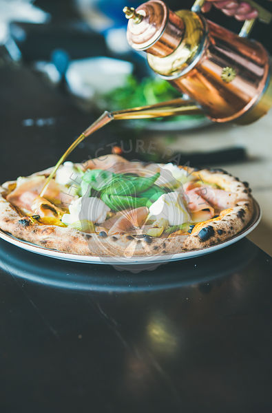 Freshly baked Italian pizza with ham, artichokes served in restaurant
