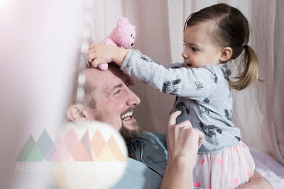 Happy father playing with toddler daughter in toy teepee
