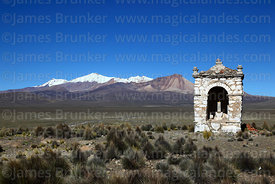 Cairn on hilltop near Lagunas village, volcanos on Chile border in background, Sajama National Park, Bolivia