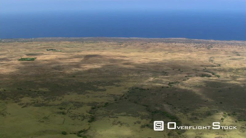 Flying seaward over rolling brown hills in Hawaii