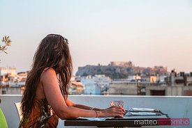 Woman at a restaurant enjoying the view of the Acropolis at sunset. Athens, Greece