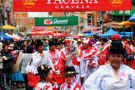 A pepino dancing with cholitas during parades for the Entierro del Pepino, La Paz, Bolivia