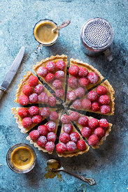 Freshly baked custard tart decorated with fresh raspberries on a table