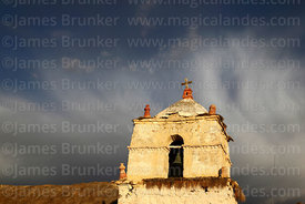 Rustic church belfry in Parinacota village and storm cloud, Lauca National Park, Region XV, Chile