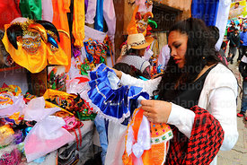 A woman looks at a pepino outfit outside a costume hire / rental shop, La Paz, Bolivia