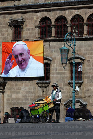 Ice cream seller in front of banner for visit of Pope Francis, Plaza San Francisco, La Paz, Bolivia