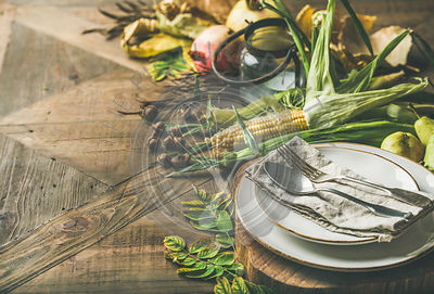Plate, cutlery, candle holder, Autumn seasonal vegetables, fruit and fallen yellow leaves for decor over wooden background